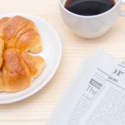 「クロワッサンとコーヒー、英文の新聞」の写真素材