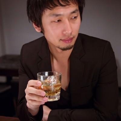 「バーラウンジでお酒を愉しむ男性」の写真素材