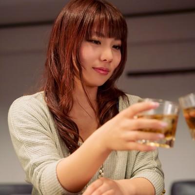 バーカウンターで隣の方と乾杯する女性の写真