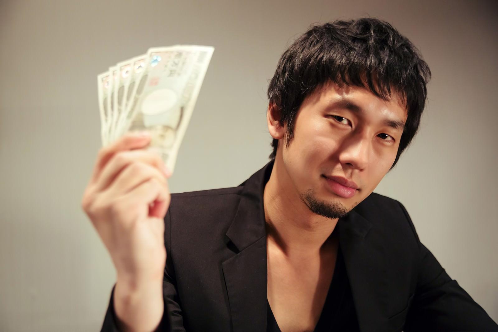 「萬券を見せつける闇金風の男性」の写真[モデル:大川竜弥]
