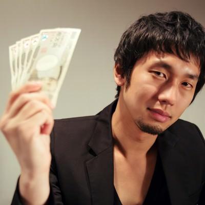 「萬券を見せつける闇金風の男性」の写真素材