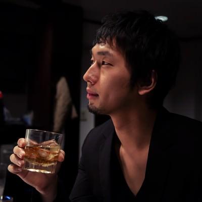 「隠れ家的なお店でお酒を愉しむIT長者風の男性」の写真素材