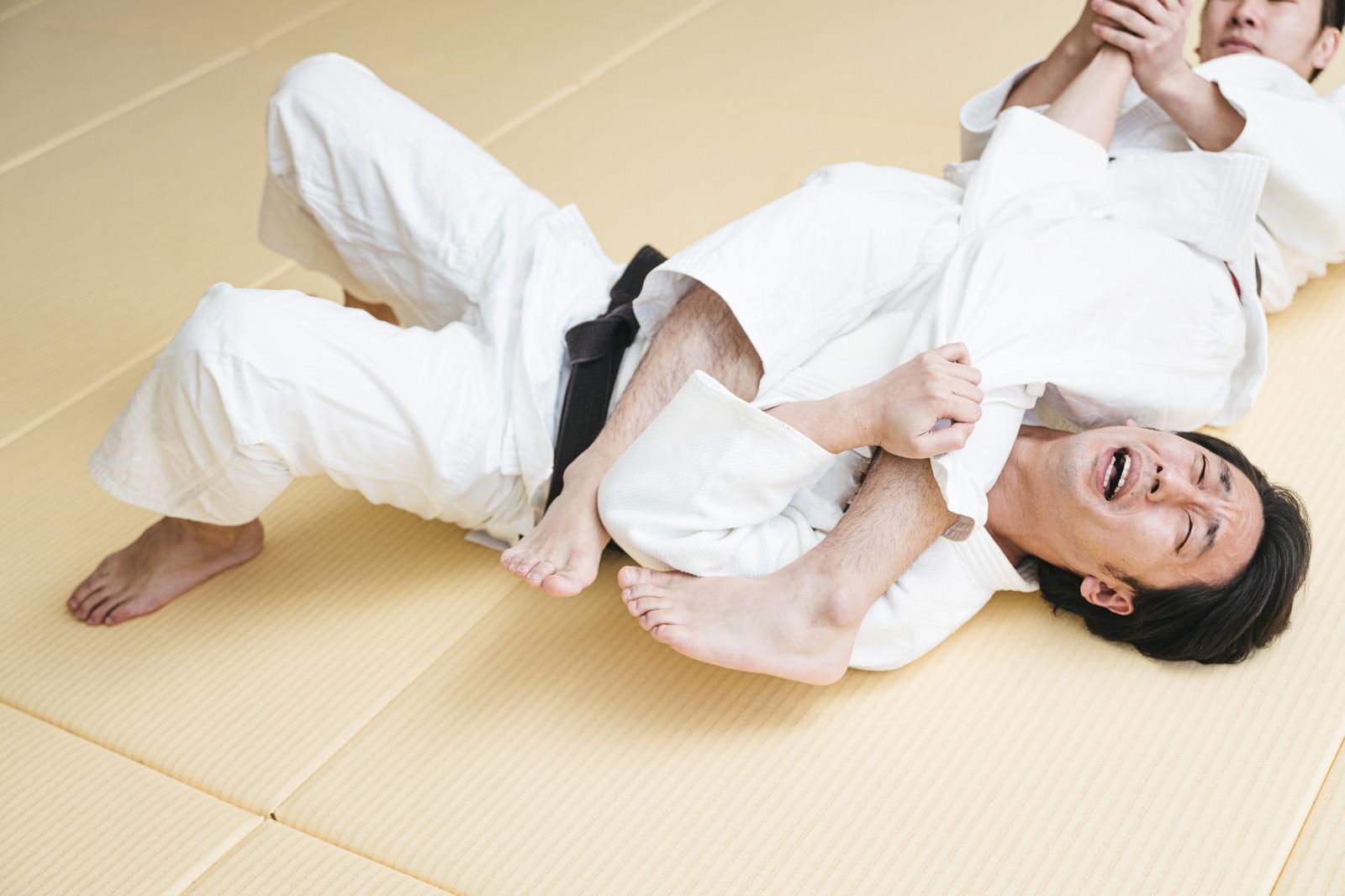 「腕ひしぎ十字固めに悶える柔道選手」の写真[モデル:大川竜弥]
