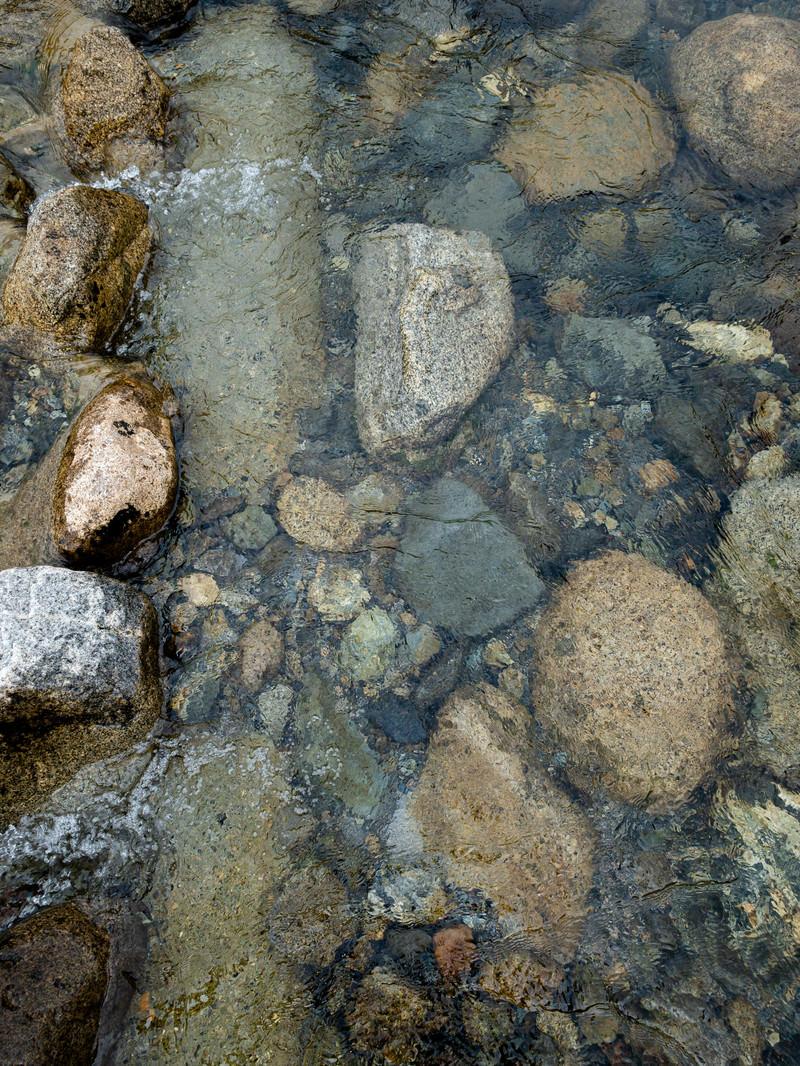 「底の石ころが透き通る水面」の写真