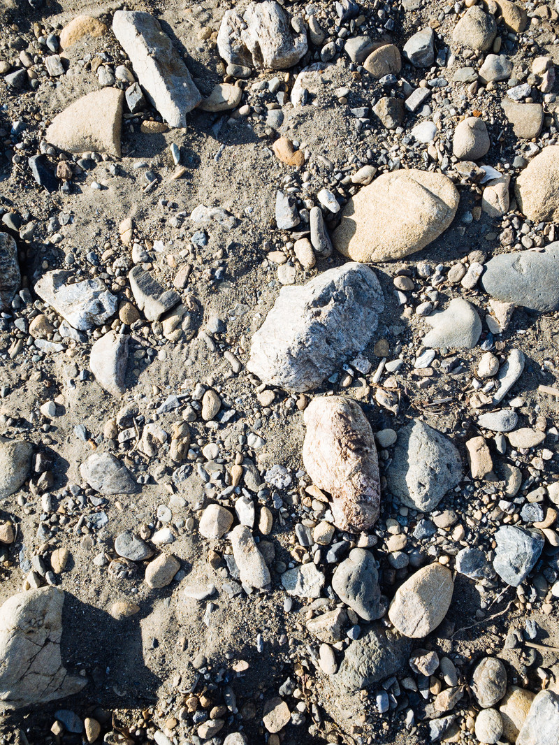 「砂地に残る大中小の石(テクスチャ)」の写真
