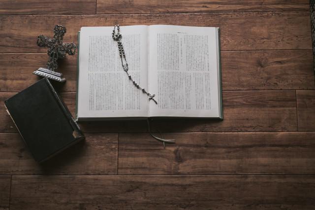 木目板の上に置かれた聖書とロザリオの写真