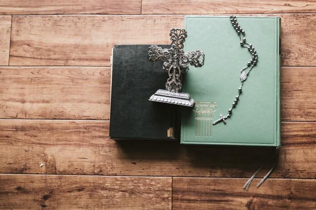 聖書とロザリオと燭台の写真