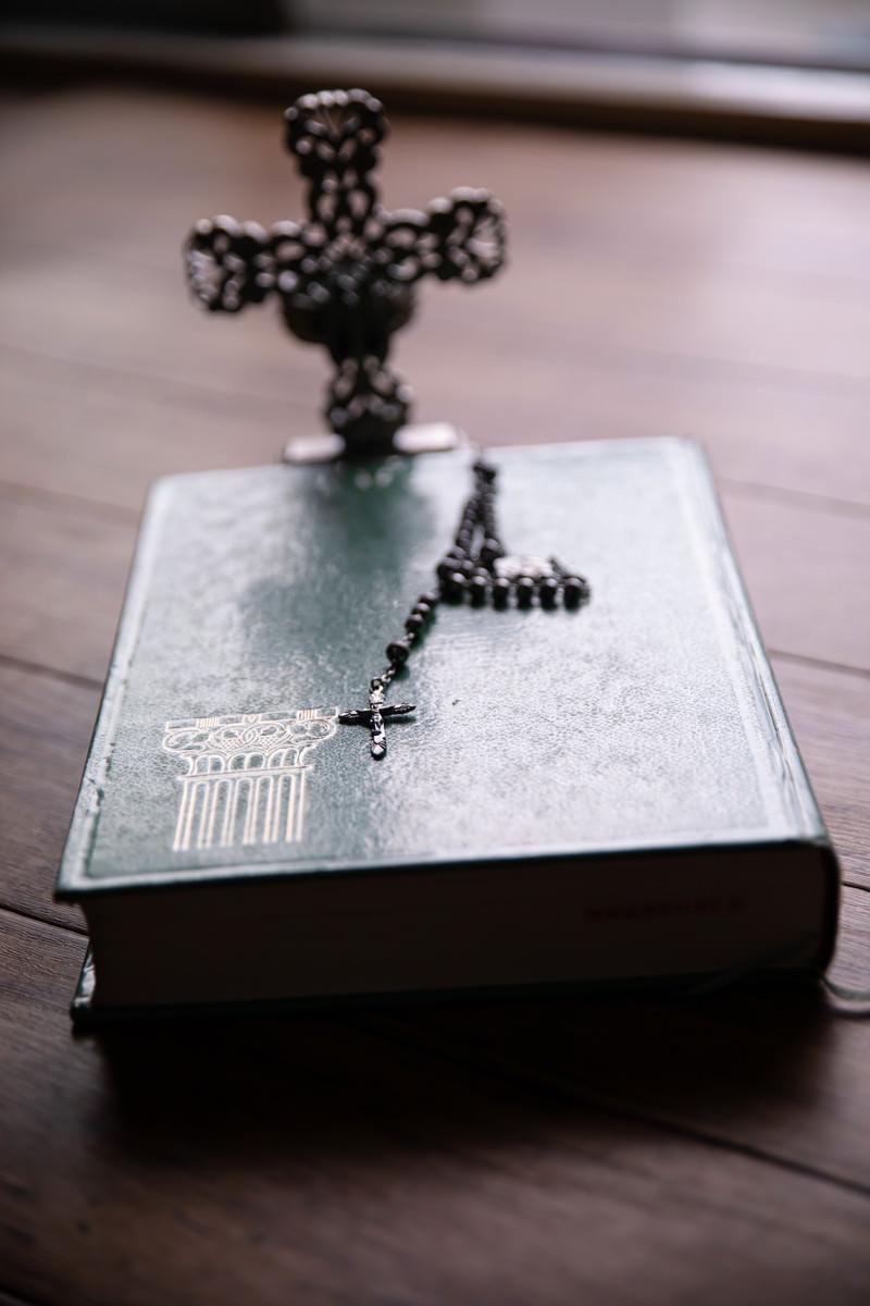 「窓際に置かれた聖書の上のロザリオ」の写真