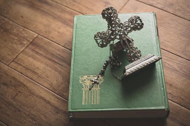 聖書の上の十字架の燭台とチャームの写真