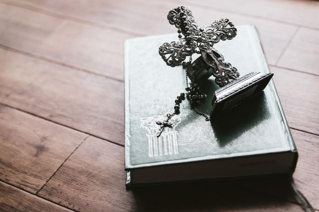 十字架の燭台とロザリオ(聖書)の写真