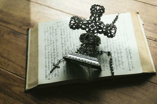 窓辺に置かれた十字架の燭台とロザリオの写真