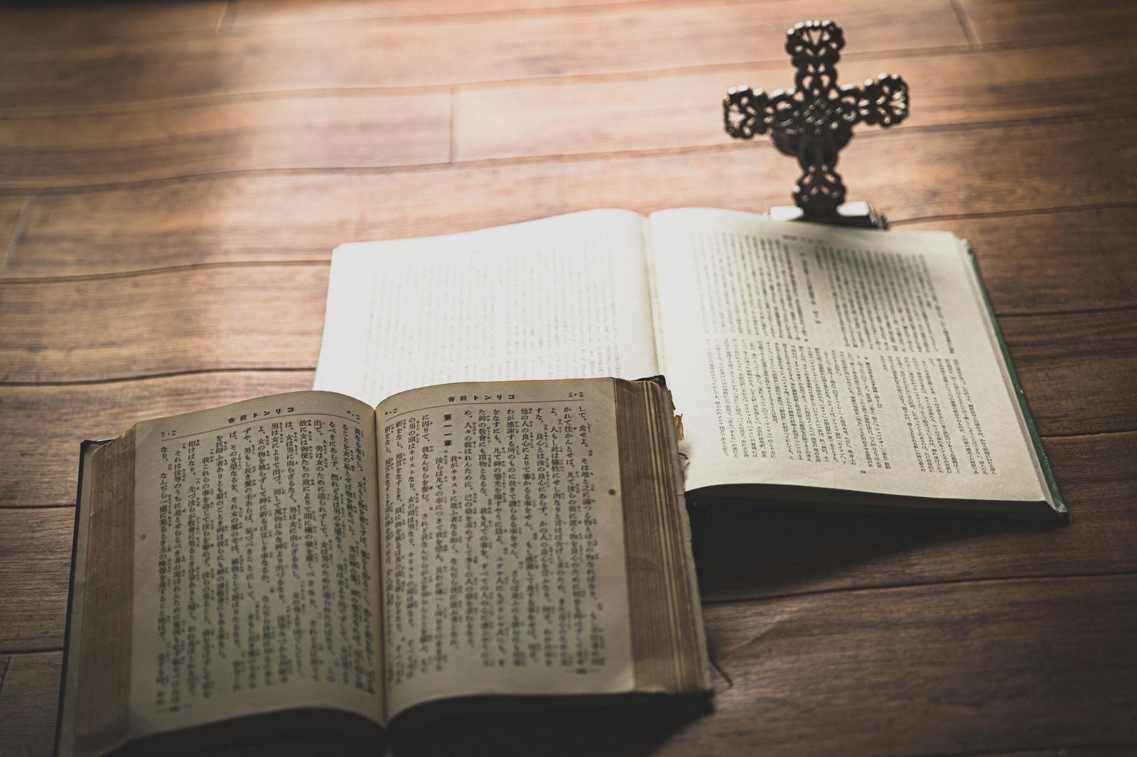 「窓際に置かれた聖書と十字架の燭台」の写真