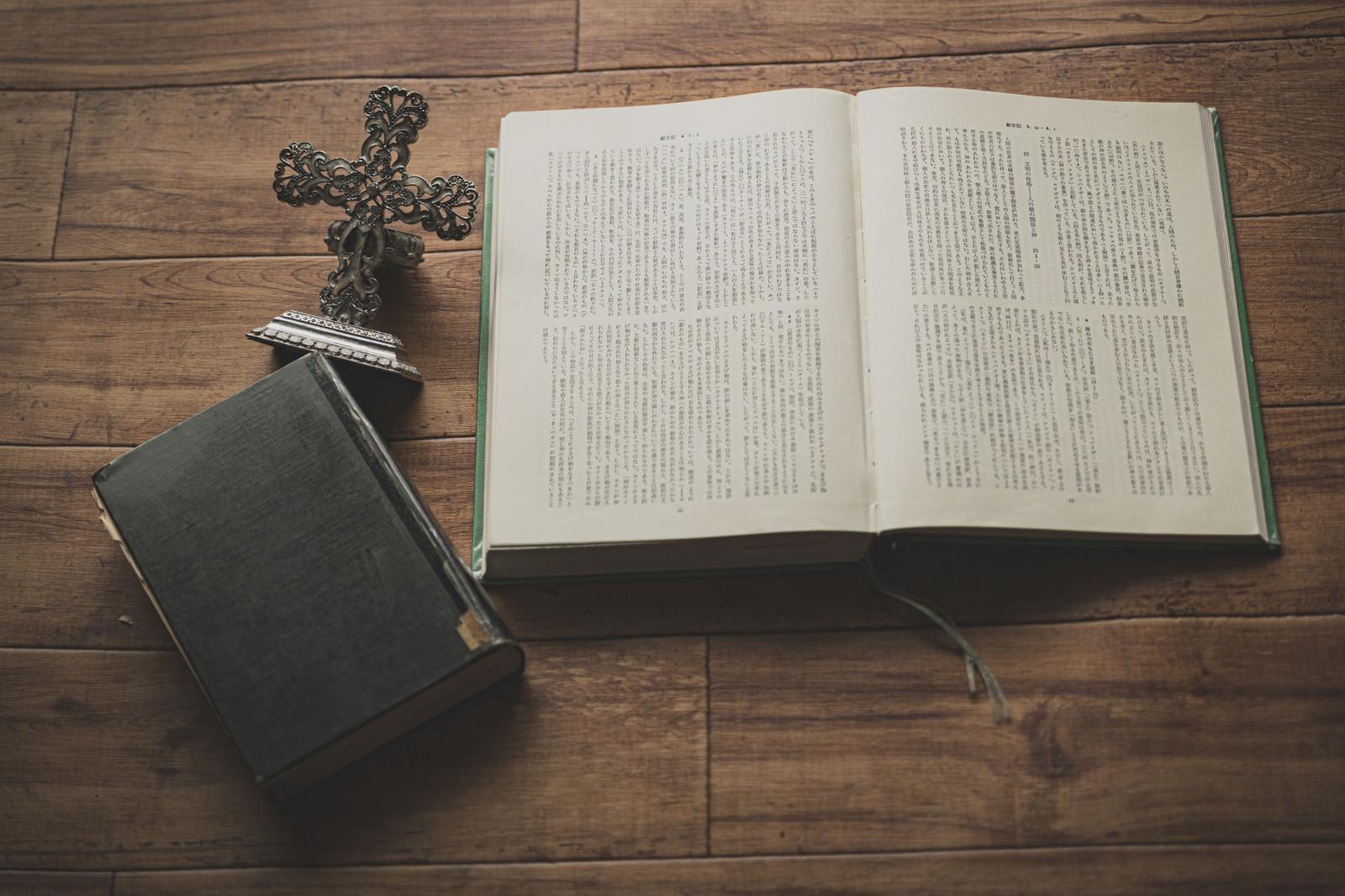 「無造作に置かれた十字架の燭台と聖書」の写真