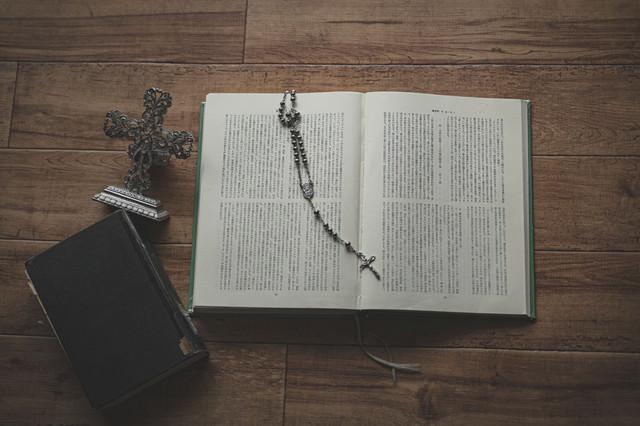 開いた聖書に置かれたロザリオの写真