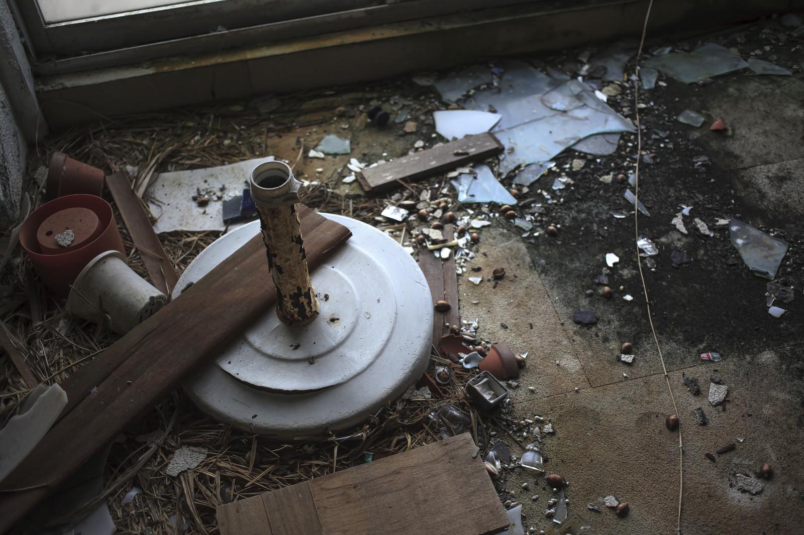 「割れたガラスやゴミが散らばる廃墟の床」の写真