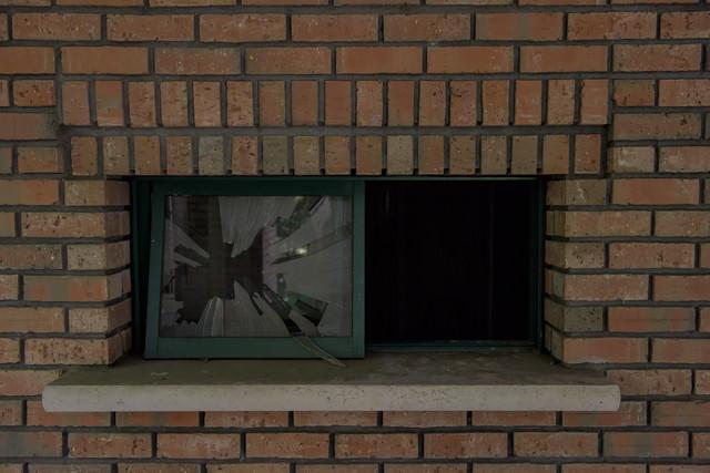 レンガと割れたガラス窓の写真