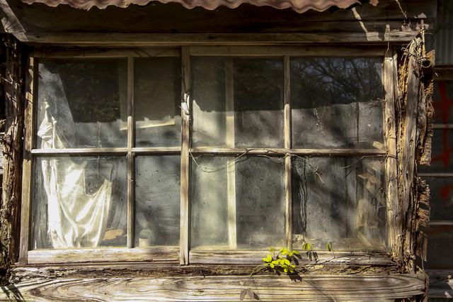 木造の廃屋の窓の写真