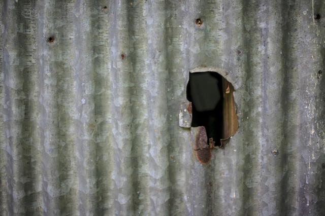 穴の空いたトタンの写真