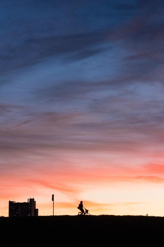 土手を走る自転車の夕焼けシルエットの写真