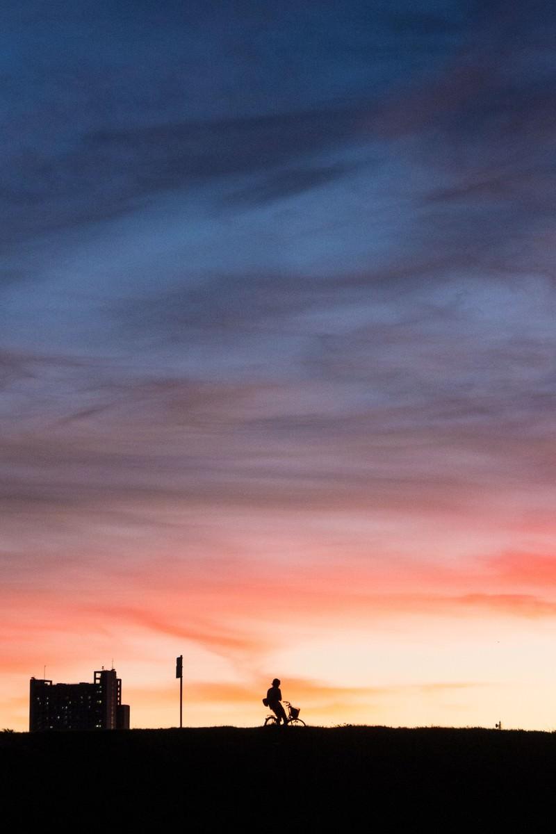 「土手を走る自転車の夕焼けシルエット」の写真