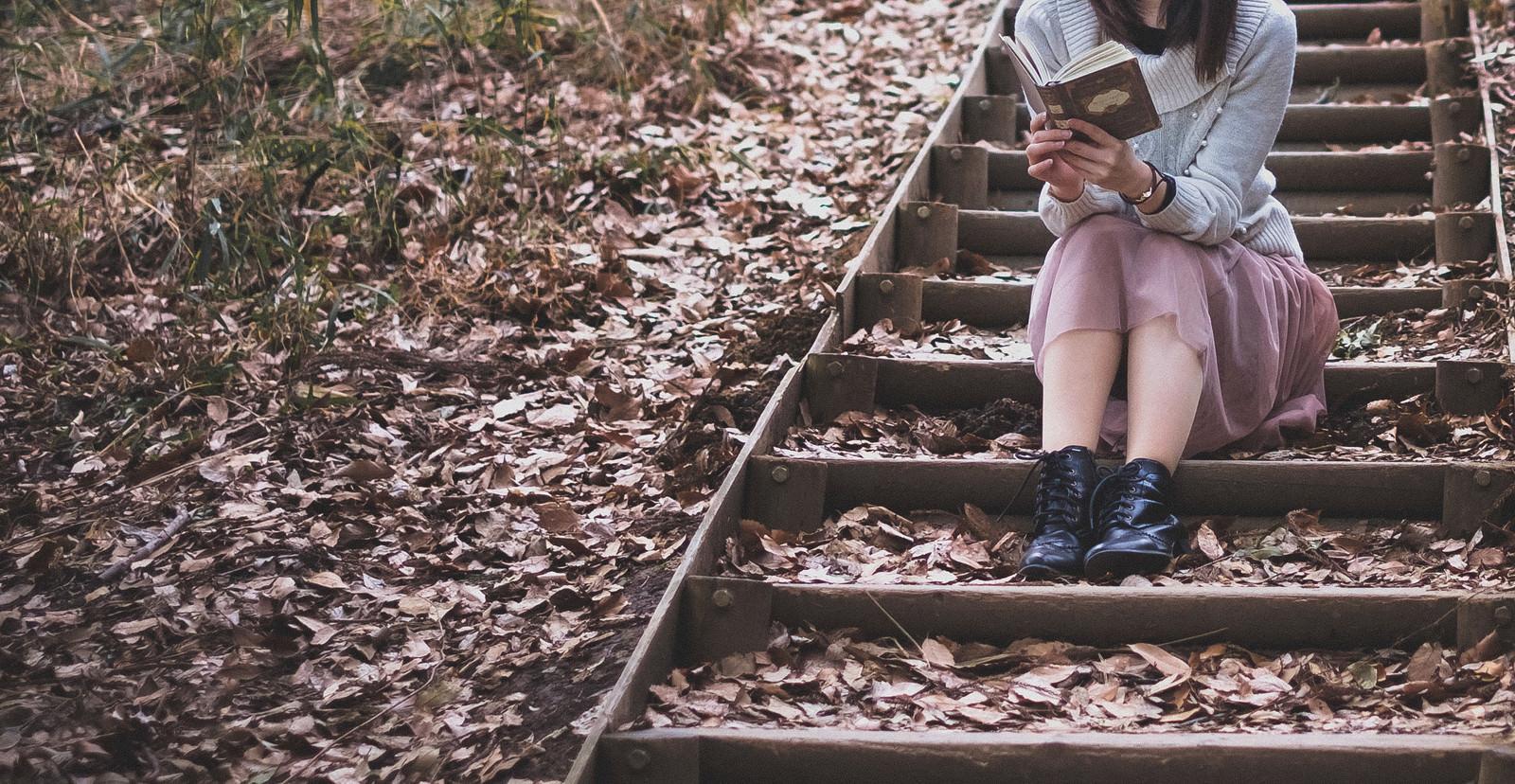 「落ち葉が積もる階段で読書に耽る女性」の写真