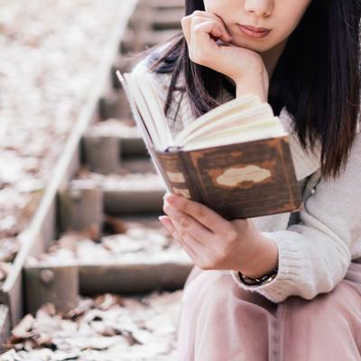 屋外で洋書を読む女性の写真