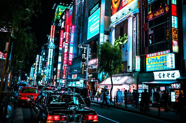 繁華街のネオンと路肩に停めるタクシー(新橋)の写真