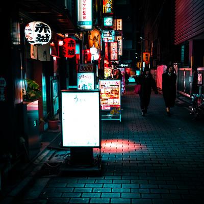 飲み屋の看板と提灯が並ぶ裏路地の写真