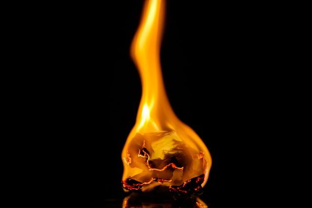 揺れる炎にともし火の写真