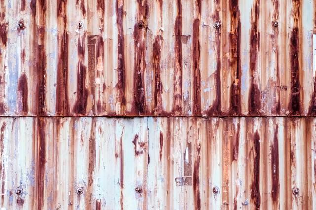 塗装が剝がれて錆が目立つトタンの壁(テクスチャー)の写真