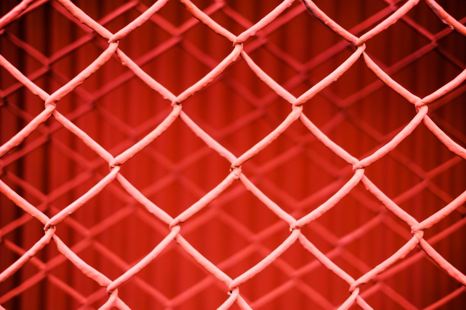 「重なった金網フェンス(赤)」の写真