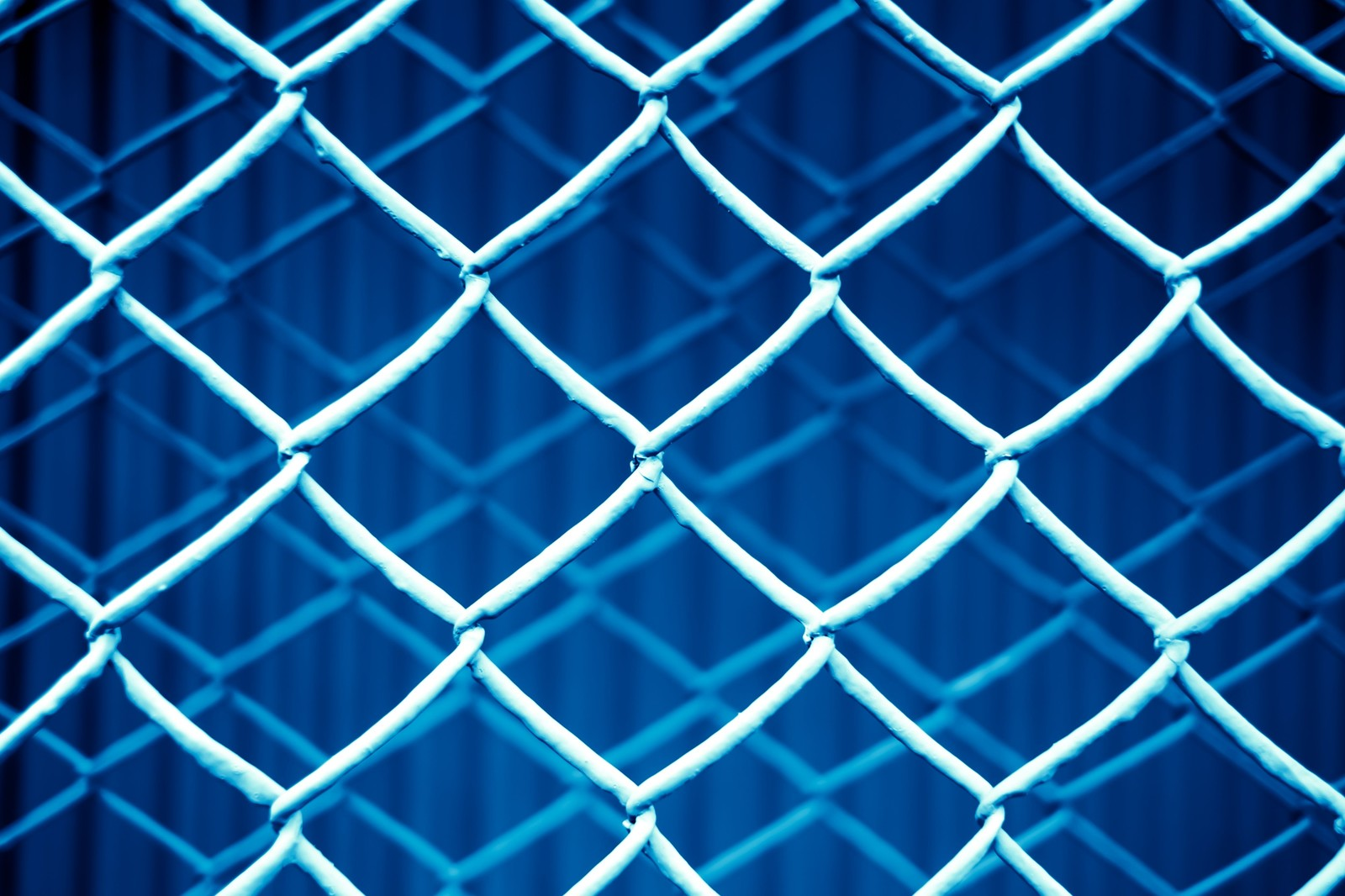 「重なった金網フェンス(青)」の写真