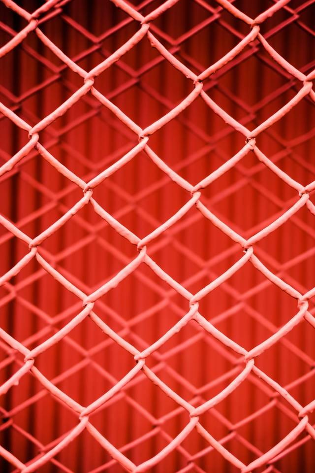 重なる赤いフェンスのテクスチャーの写真