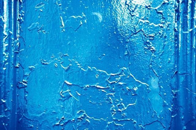 錆びた壁に上から青いペンキを塗るの写真