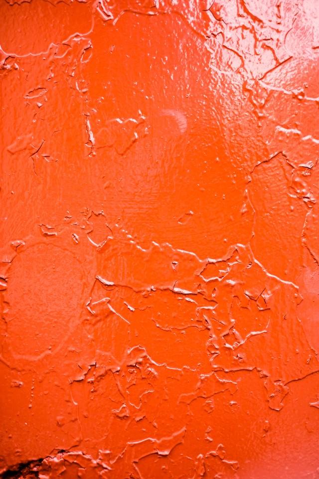 錆びでひび割れた赤い壁の写真
