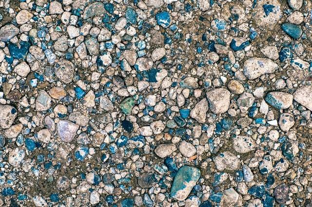 上から圧がかかった地面と小石(テクスチャー)の写真