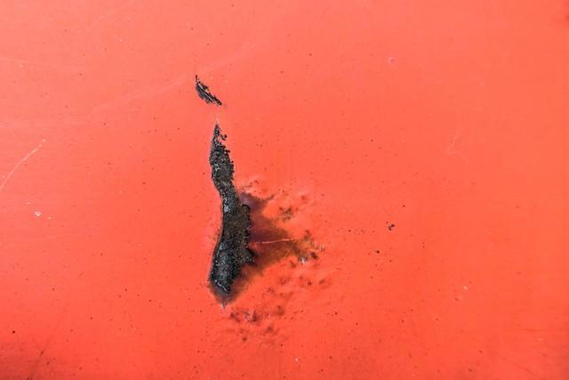 塗装が剥がれて黒く変色した壁の写真