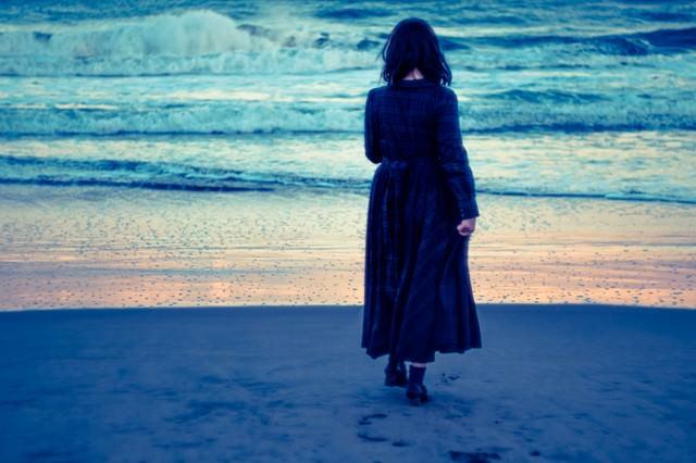 波打ち際、寂しげな女性の写真