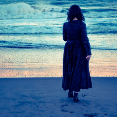 「波打ち際、寂しげな女性」の写真素材