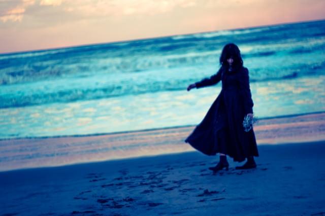 浜辺を彷徨う黒服の女性の写真