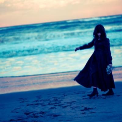 「浜辺を彷徨う黒服の女性」の写真素材