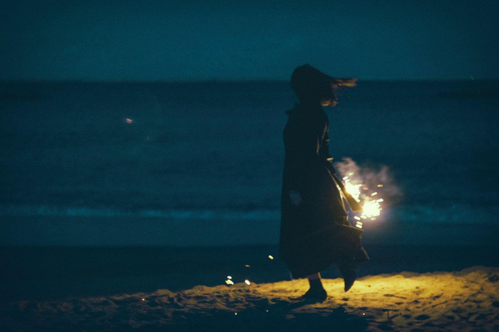 「夜の浜辺で手持ち花火と女性のシルエット」の写真