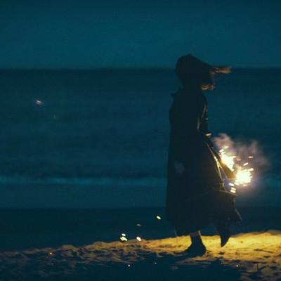 「夜の浜辺で手持ち花火と女性のシルエット」の写真素材