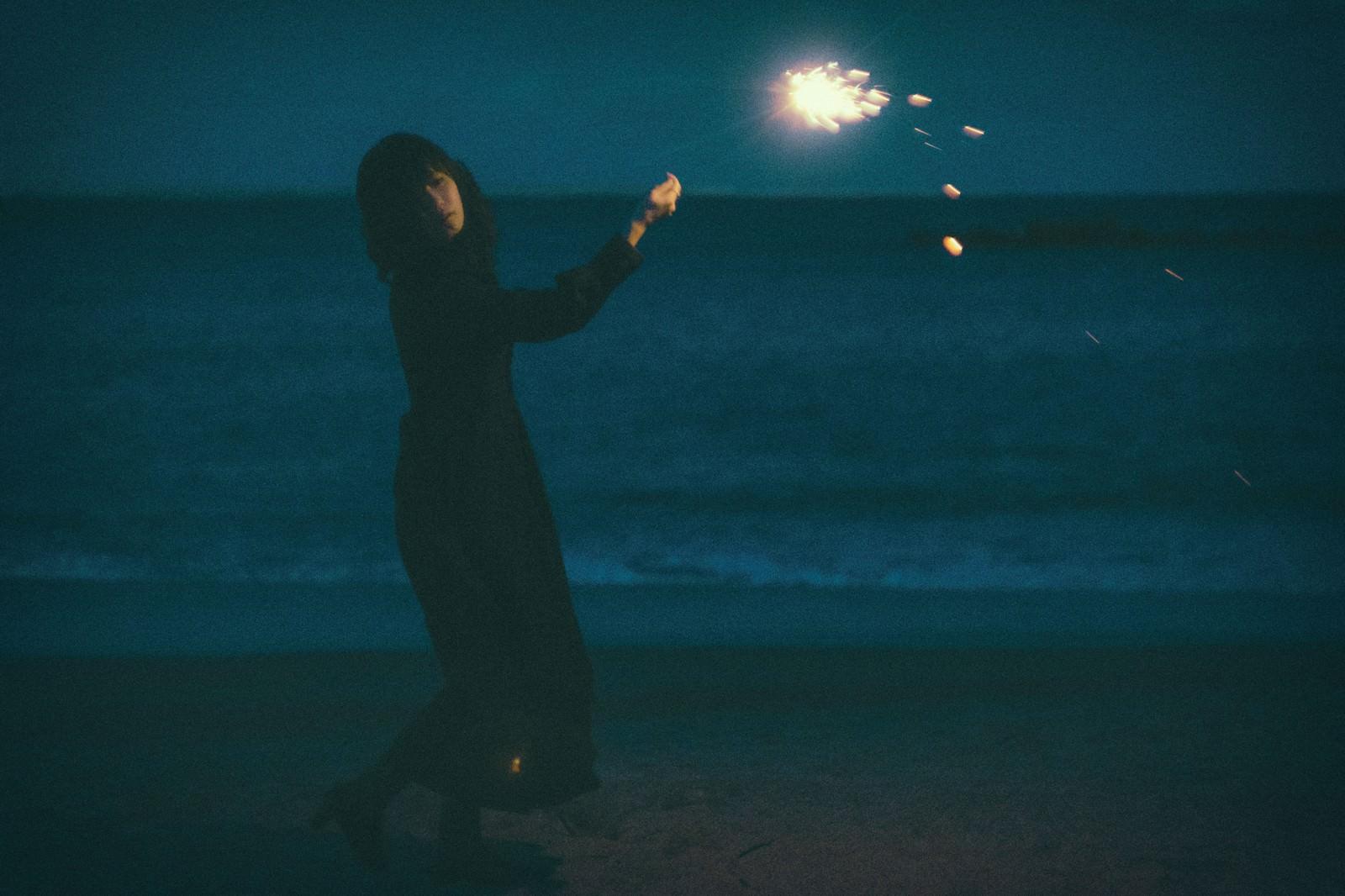 「悲しい表情で手持ち花火」の写真