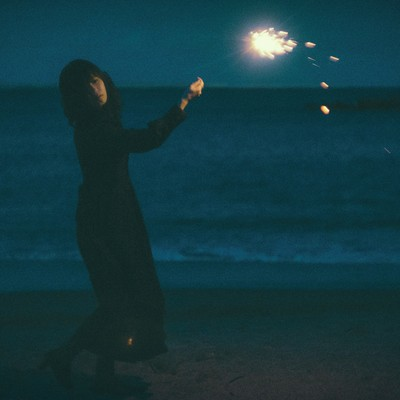 「悲しい表情で手持ち花火」の写真素材