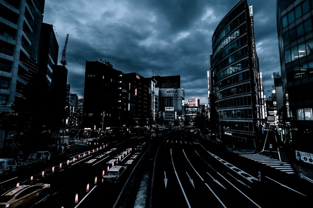 曇り空と日が落ちた新宿駅前の写真