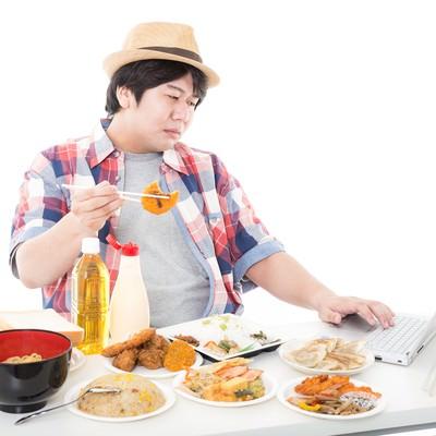 「コロッケを食べながらコロッケの画像をネットで検索する休日のパパ」の写真素材