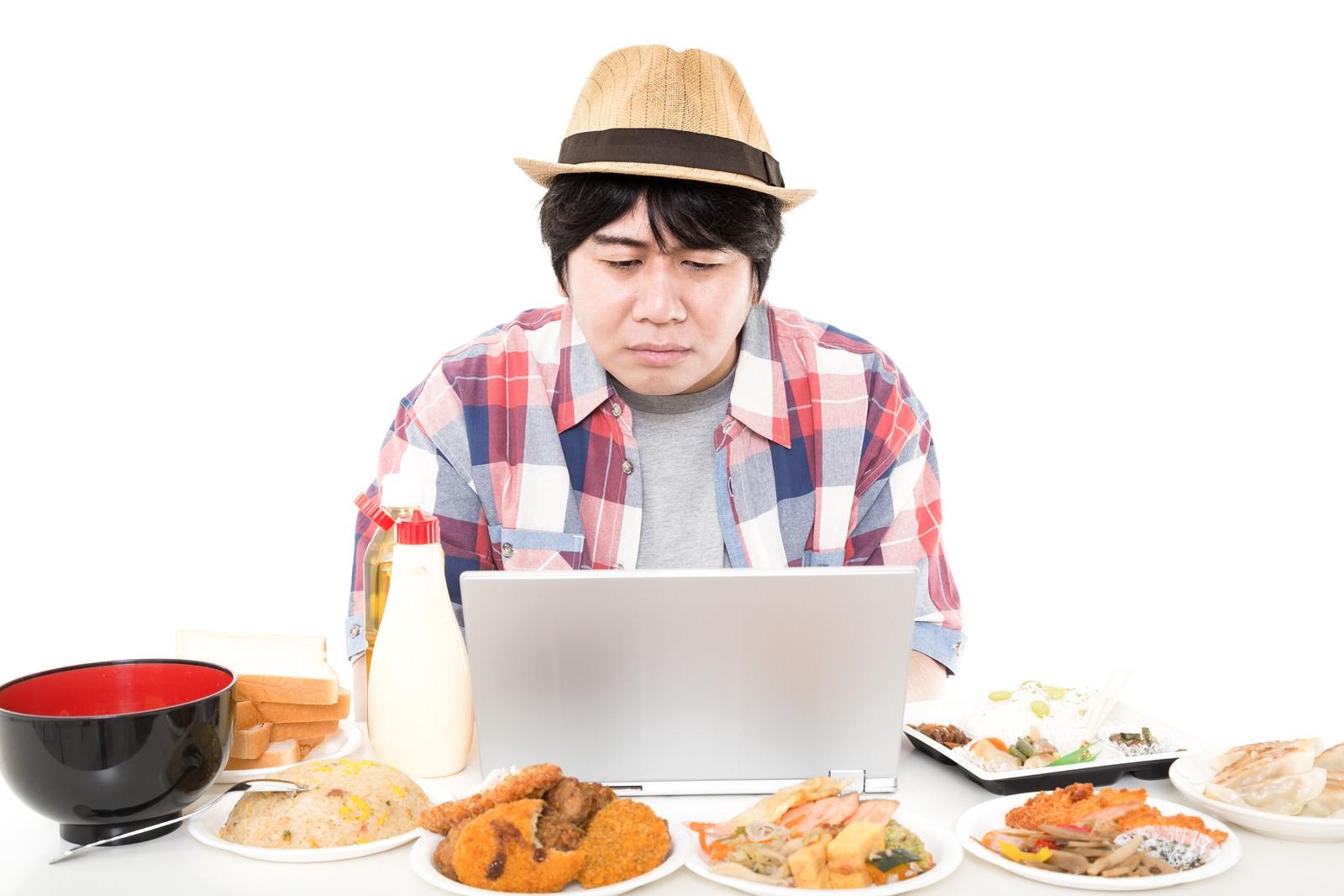 「周りにある食事が気になって仕事が手に付かないインテリ肥満」の写真[モデル:あまのじゃく]