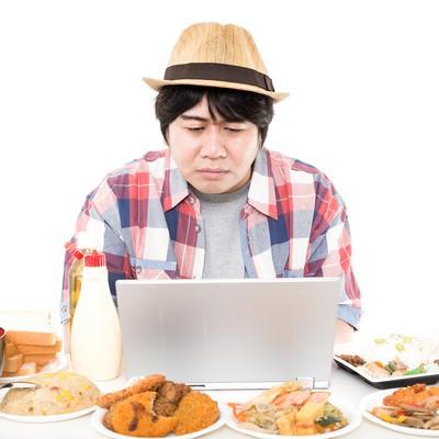 「周りにある食事が気になって仕事が手に付かないインテリ肥満」の写真素材