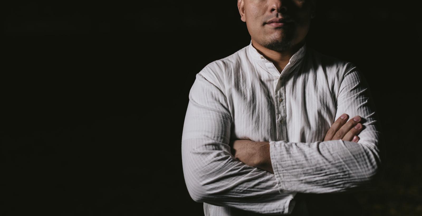 「暗闇の中、立ちはだかる男性」の写真